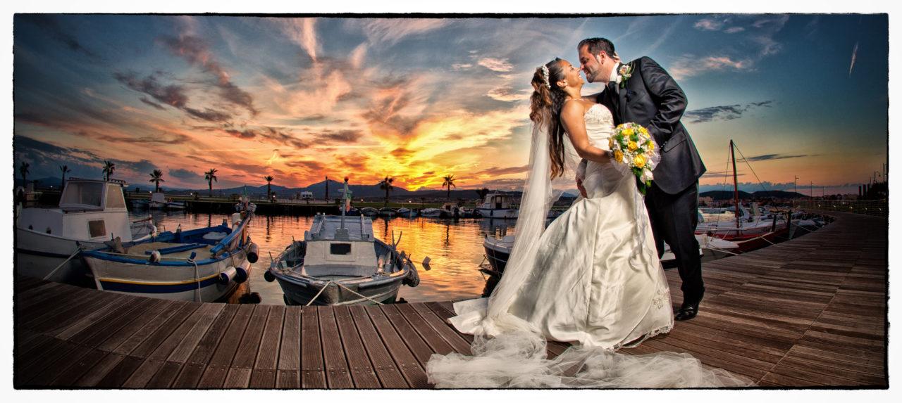 Sposi in passerella con barche attraccate al molo. Foto scattata da Giuseppe Ortu fotografo fine art specializzato in matrimoni a Olbia.