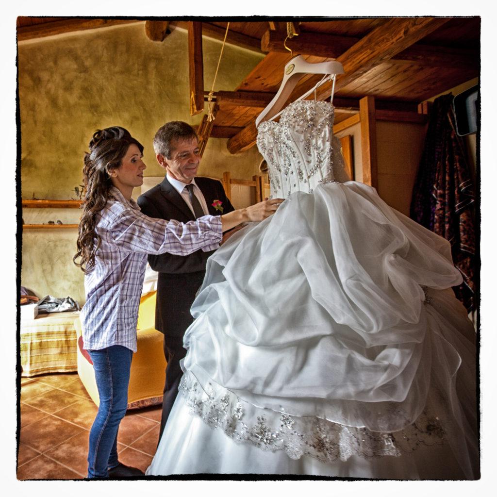 Sposa che guarda il suo abito prima di indossarlo. Foto scattata in stile Fine Art dal fotografo olbiese Giuseppe Ortu. Fotografo matrimoni Olbia.