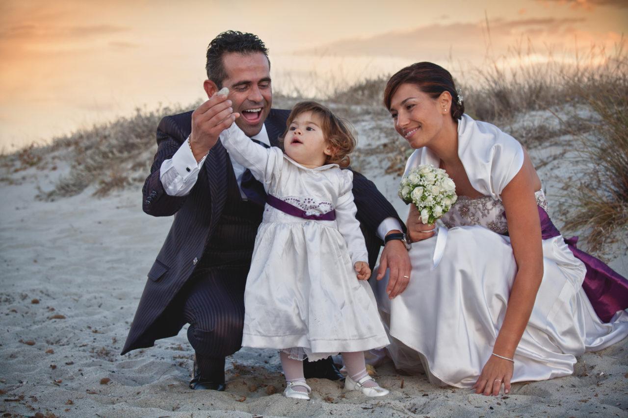Famiglia felice in spiaggia nel giorno del matrimonio. Foto scattata da Giuseppe Ortu fotografo esperto in matrimoni a Olbia