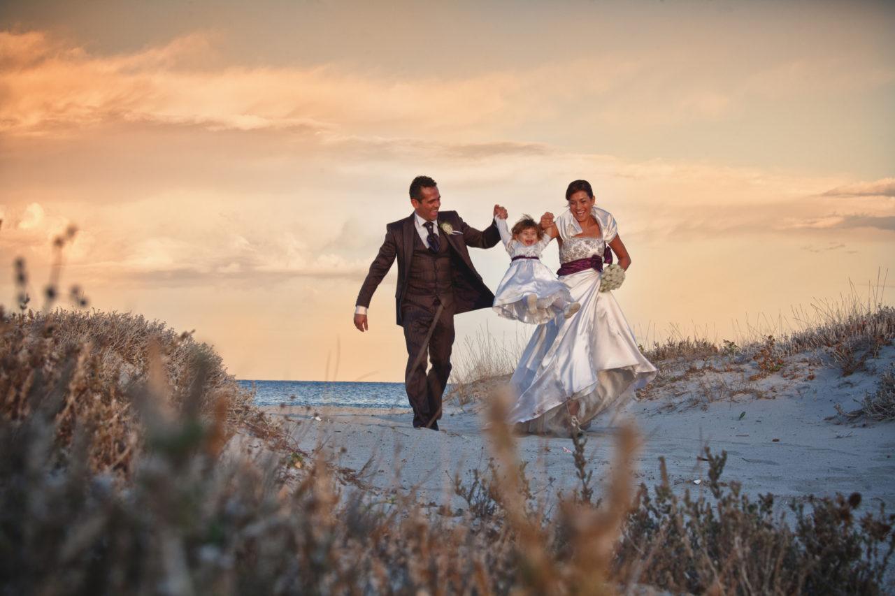 Famiglia felice tra le dune di una spiaggia olbiese. Fotografia scattata da Giuseppe Ortu esperto in matrimoni a Olbia.
