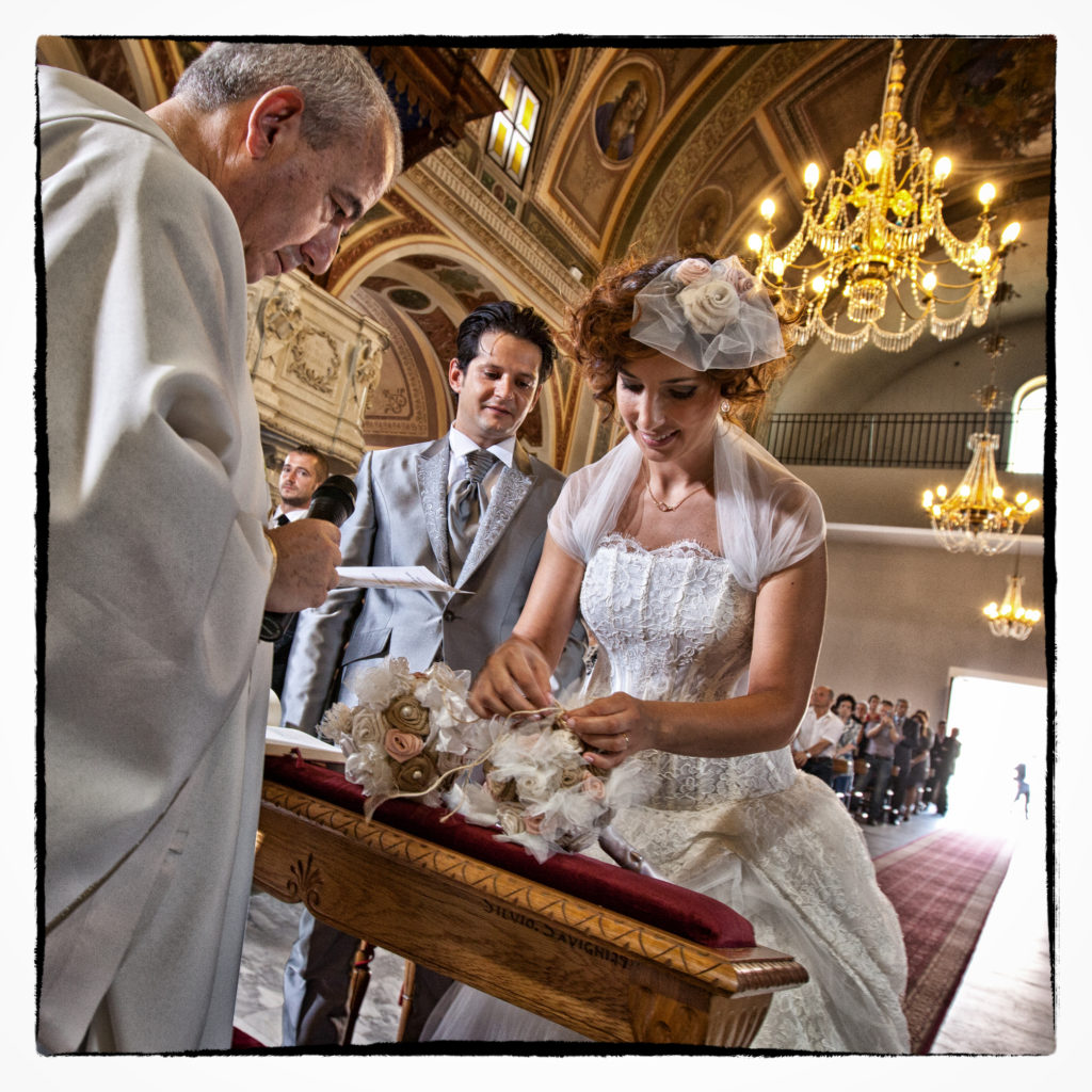 Prete che celebra messa nunziali a sposi. Foto scattata da Giuseppe Ortu fotografo fine art specializzato in matrimoni a Olbia.