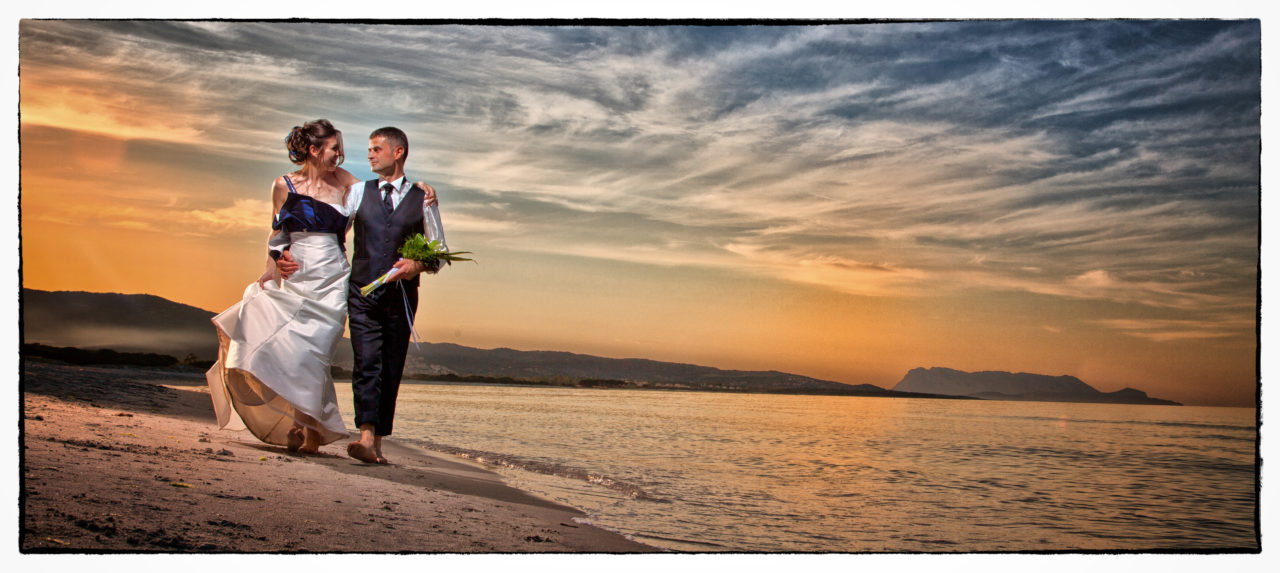 Sposi che passeggiano sul bagnasciuga. Foto scattata in stile Fine Art dal fotografo olbiese Giuseppe Ortu. Fotografo matrimoni Olbia.