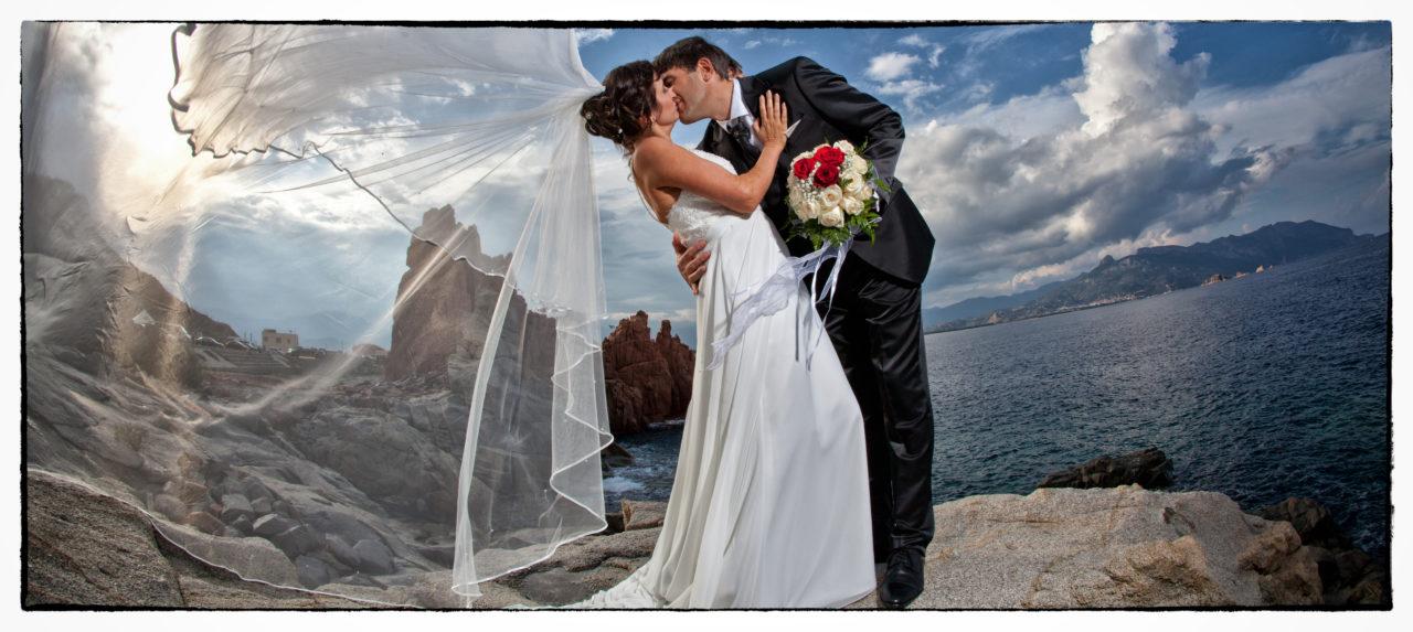 Sposi che si baciano sulla scogliera. Foto scattata in stile Fine Art dal fotografo olbiese Giuseppe Ortu. Fotografo matrimoni Olbia.