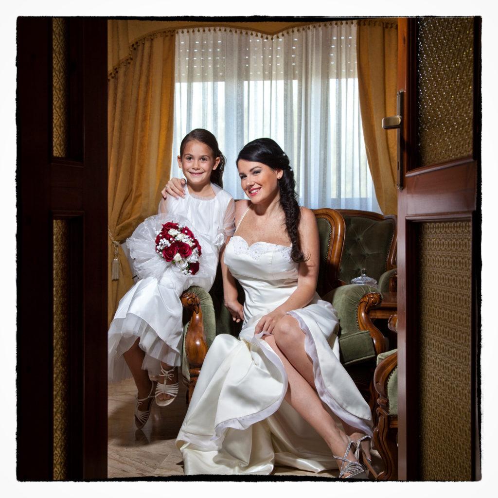 Sposa in camera da letto con damigella. Foto scattata in stile Fine Art dal fotografo olbiese Giuseppe Ortu. Fotografo matrimoni Olbia