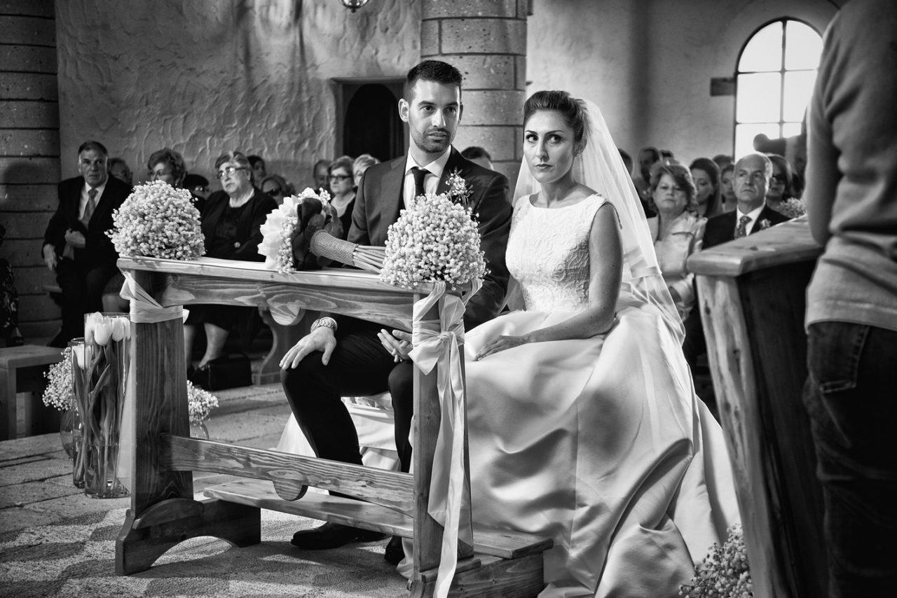 Sposi in chiesa dietro il banchetto. Foto scattata da Giuseppe Ortu fotografo specializzato in matrimoni a Olbia