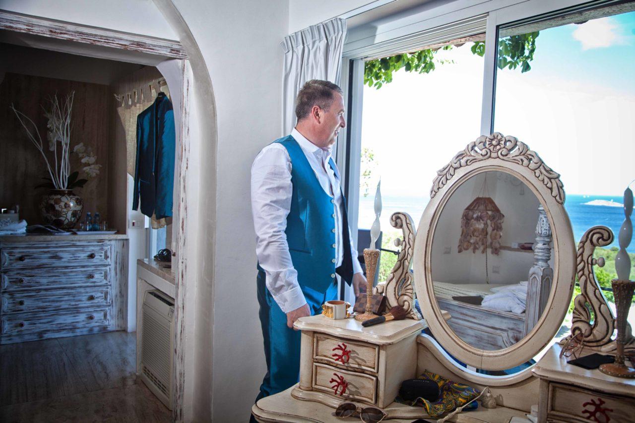 Sposo che guarda il mare dalla finestra. Foto scattata da Giuseppe Ortu fotografo specializzato in matrimoni a Olbia.