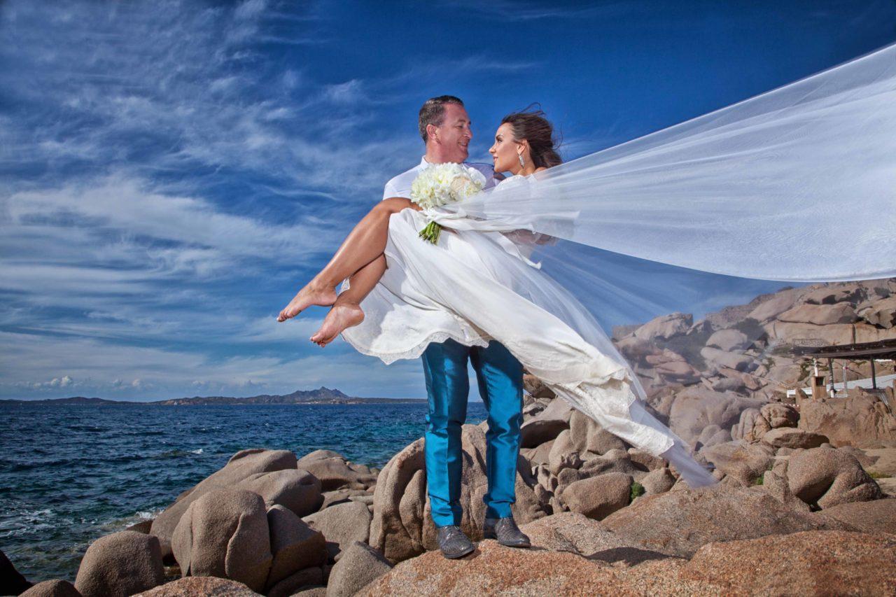 Sposa in braccia allo sposo sugli scogli in riva al mare. Foto scattata da Giuseppe Ortu fotografo specializzato in matrimoni a Olbia.