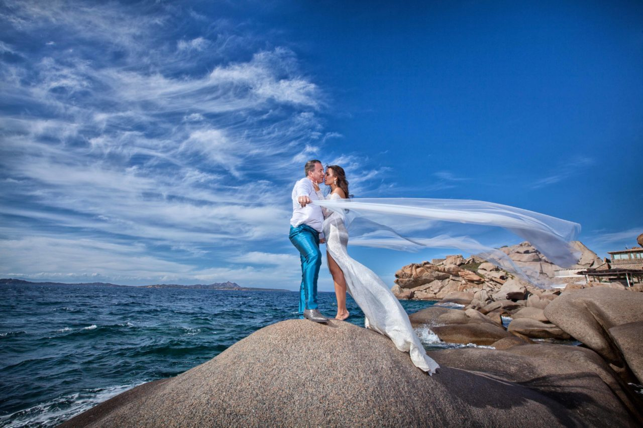Coppia di sposi che si bacia sugli scogli in riva al mare. Foto scattata da Giuseppe Ortu fotografo specializzato in matrimoni a Olbia.
