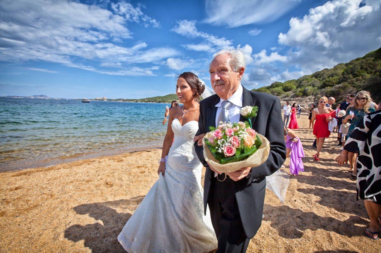 Sposa accompagnata sulla spiaggia. Fotografia scattata da Giuseppe Ortu fotografo specializzato in matrimoni a Olbia.