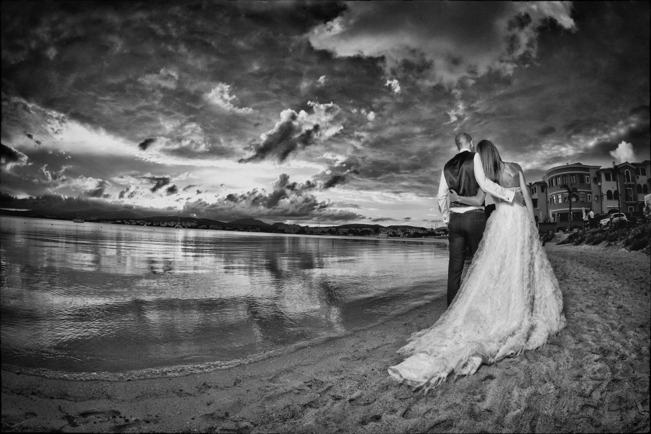 Sposini in riva al mare in bianco e nero. Foto scattata da Giuseppe Ortu fotografo specializzato in matrimoni a Olbia